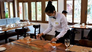 Une étudiante de PSE en train de dresser une table dans le restaurant d'application rénové de PSE