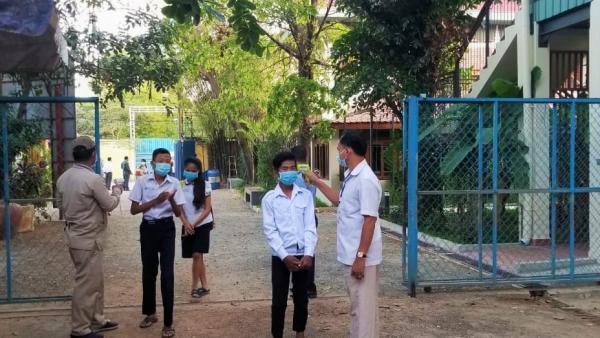 Les gardes prennent la température de tous les élèves à l'entrée de PSE