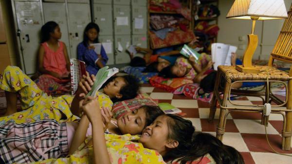 Des fillettes du pensionnat en train de lire dans leur chambre