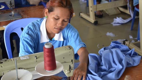 Une couturière de l'atelier couture de PSE confectionne une chemise