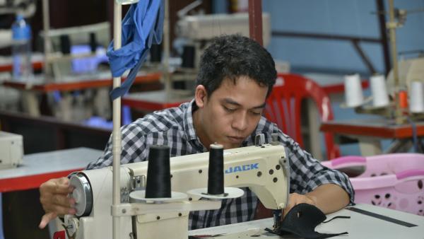 Un couturier de l'atelier couture de PSE confectionne un masque