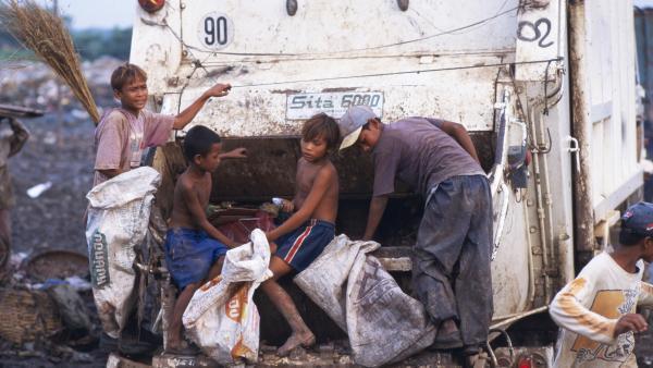 Des enfants à l'arrière d'un camion sur la décharge