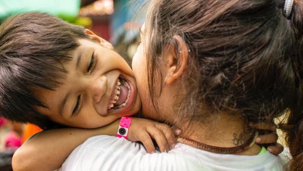 Une monitrice prend dans ses bras un enfant aidé par PSE
