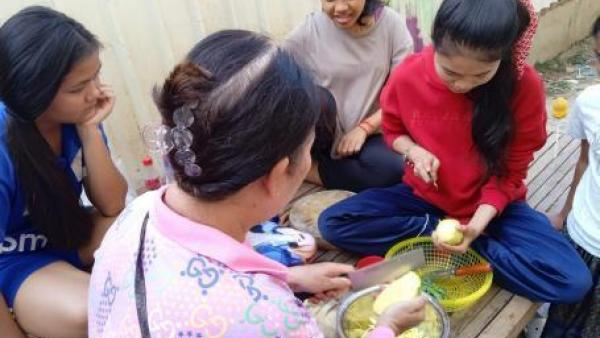 Karuna cuisine avec sa mère d'accueil et d'autres jeunes pris en charge avec elle