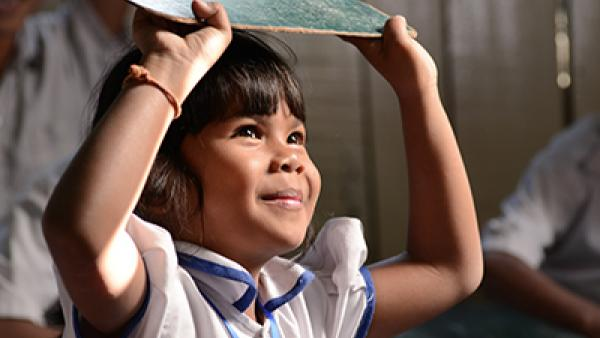 En classe, une petite fille tient une ardoise au-dessus de sa tête