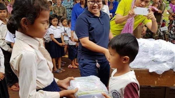 Leakhéna en train de distribuer du matériel scolaire à deux enfants pris en charge par PSE