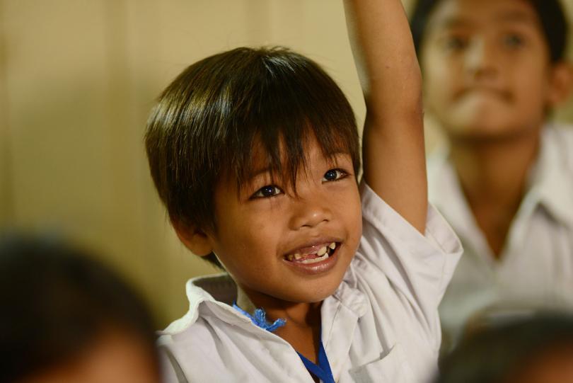 Un petit garçon en classe à PSE lève le doigt