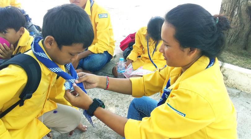 Une scout aidant un enfant à nouer son foulard