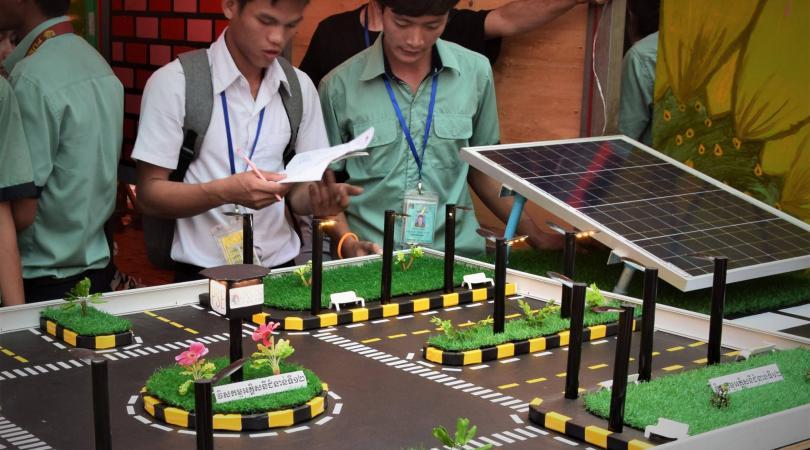 Un élève s'intéresse à la maquette fonctionnant à l'électricité solaire de nos étudiants en électricité